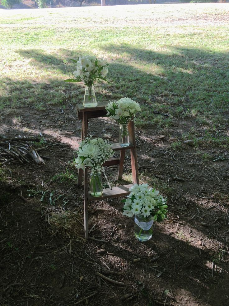 vintage 3 tiered little wooden ladder with a collection of original milk pints filled with chrysanthemum,alstromeria,gyp and mini roses