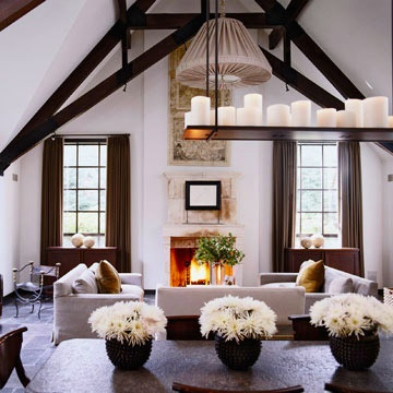 Firelight, dozens of candles on a tray suspended from the ceiling beams, rustic furnishings and exposed beams