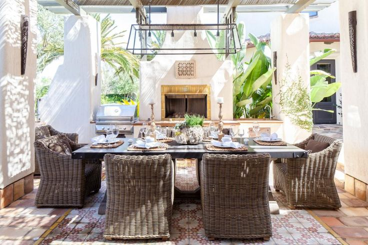 Tucked inside an elegant covered patio, this Mediterranean-style outdoor dining room will make guests line up for an invitation. Large wicker chairs and a stylish overhead light fixture provide practical comfort.