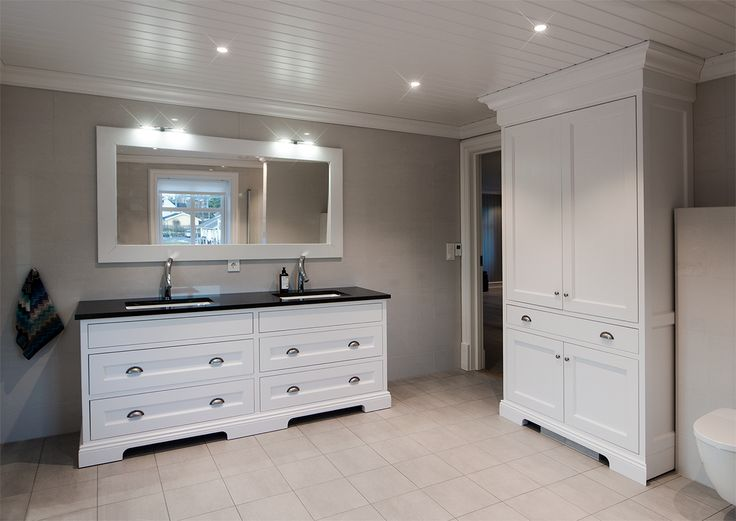 White bathroom furniture with double sinks. Worktop in black granite. Double linen closet with plenty of storage. Hand crafted by Os Trekultur.
