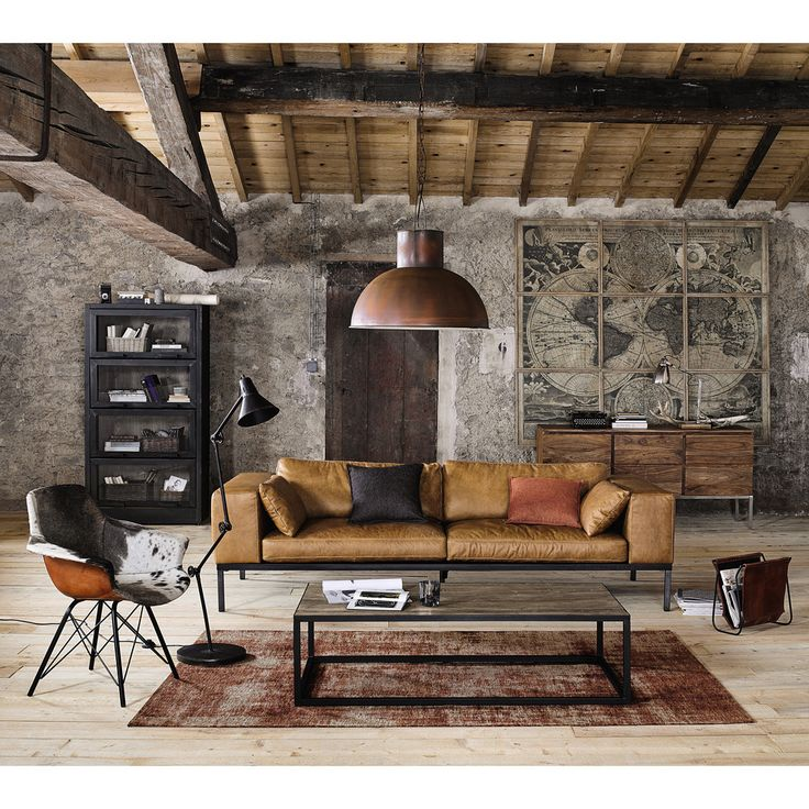 Brown textiles and tough metal create a strong industrial style living room look | Maisons du Monde