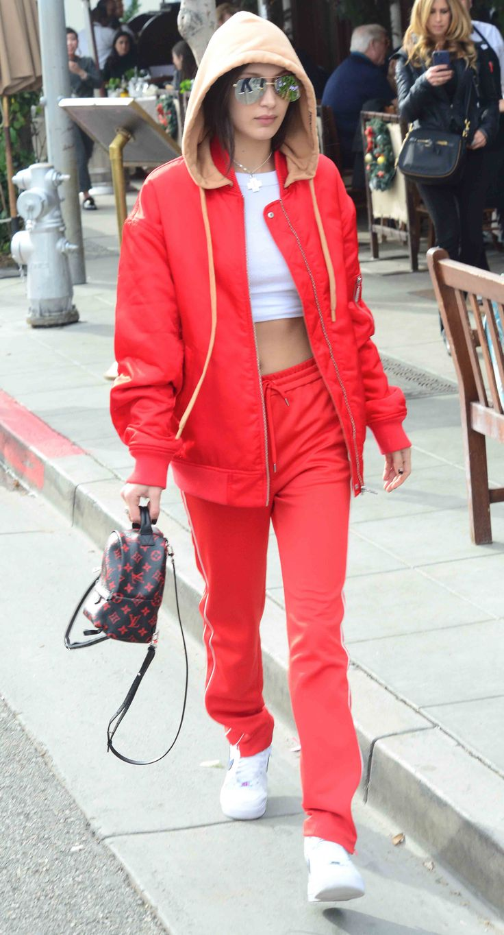 Bella Hadid wearing a red tracksuit with a Louis Vuitton backpack and white Nike sneakers