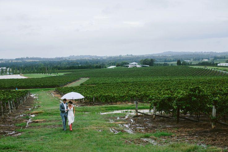 Wet weather wedding photo. Red Hunter Gumboots. Hunter Valley wedding. Image: Cavanagh Photography http://cavanaghphotography.com.au