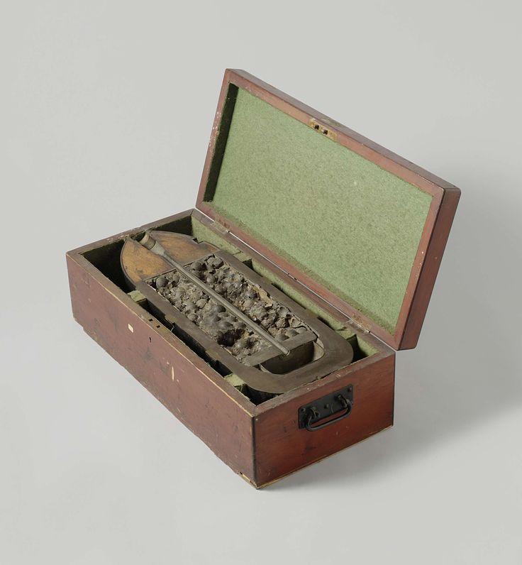 William Armstrong & Co. | 23 cm Granaat-kartets in houten kist, William Armstrong & Co., 1868 | Een halve overlangs doormidden gezaagde puntvormige 23 cm granaat-kartets, in een houten kist. De granaat is 65.8 cm lang en heeft een kaliber van 226 mm. De granaat heeft twee ringen ingeperste nokken voor een getrokken loop met zes trekkende velden, een ballistische kap gevuld met hout, een buisgat, een vuurgeleidingspijp naar de springlading in de bodem en een kartetslading van loden kogels van…