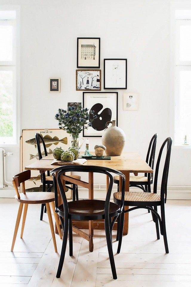 Dining Space With A Wooden Table Mismatch Chairs And Gallery Wall