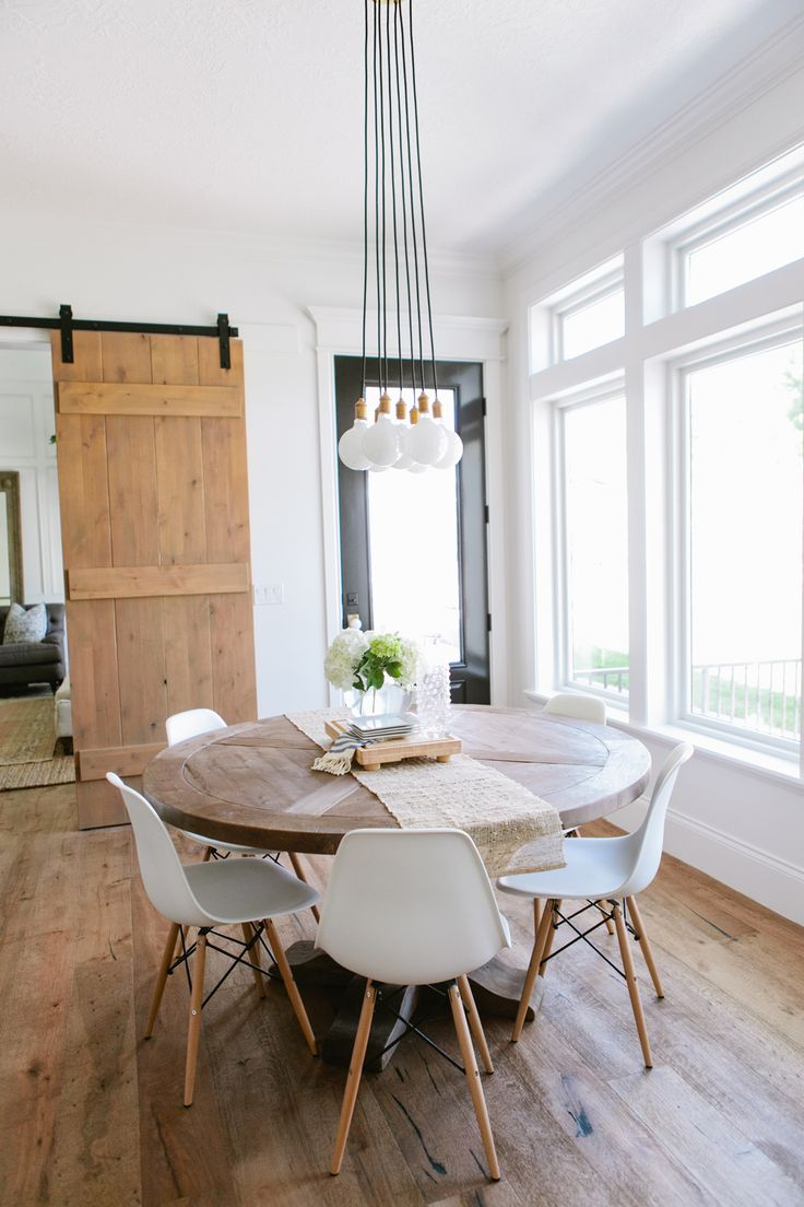 Wooden Circular Dining Table, White Chairs, Hanging Light Bulbs And Sliding  Farmhouse Door |