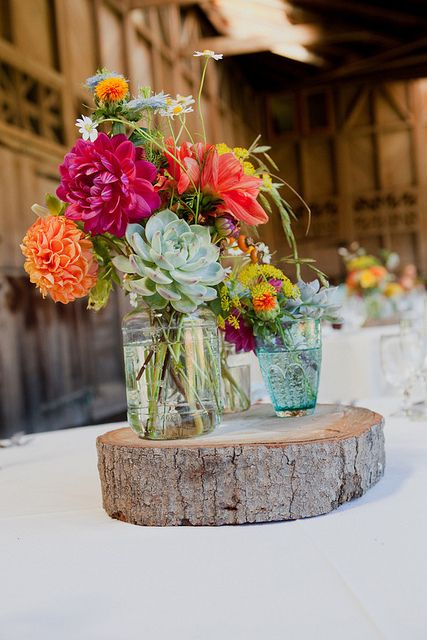 flowers in jars and vintage glasses on a slice of tree trunk