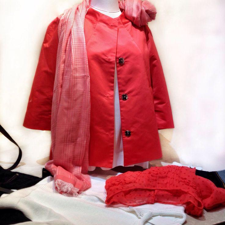 Giacca in tessuto impermeabile in rosso corallo di Add. Il golfino in cotone bianco è di RossoPuro. La camicetta in voile di seta pura color corallo con pois è di Aspesi.