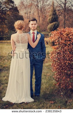 Vintage style of romantic wedding couple walking in park. Man looking at camera. Woman standing back to camera - stock photo