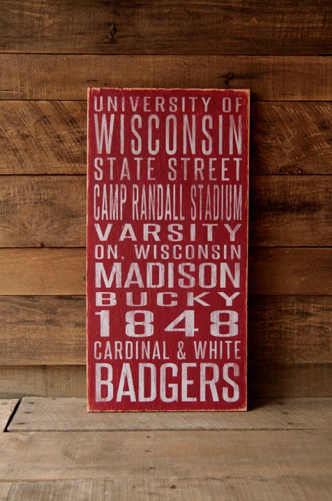 University of Wisconsin Badgers Distressed Wood Sign This University of Wisconsin Badgers subway art sign will look great in any fans home or office—from the den to the game room to the porch. Highlighting your teams landmarks, traditions, and spirit, this sign will be a great addition for any fan or alumni. The University of Wisconsin Badgers sign is shown here in Red, but can also come in Black with White writing for a more early 20th century look...just make your selection in the drop…
