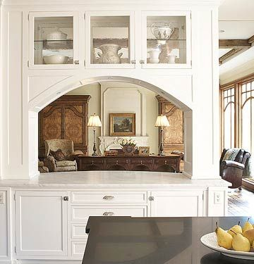 This arched opening to the living room features a marble countertop that functions as an additional island  and a convenient serving station when entertaining guests. The see-through cabinets above add character and create an eye-catching display for creamware or china or just add a transome for a cleaner more minimal look.