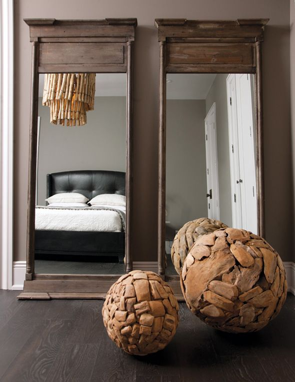Chic Bedroom Design With Gray Brown Walls Paint Color, Rustic Floor  Mirrors, Wood Chandelier And Black Leather Tufted Wingback Bed.