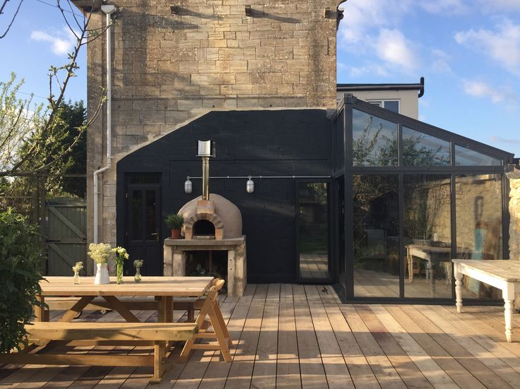 Months of hard work but it's finally finished and just in time for the summer!  Scaffold boards used for decking and inside conservatory. Outside wood/pizza oven painted in Wholemeal from B&Q masonry paint. Wall painted in Evening Shadow from B&Q masonry paint. Hand built 3m table and benches.