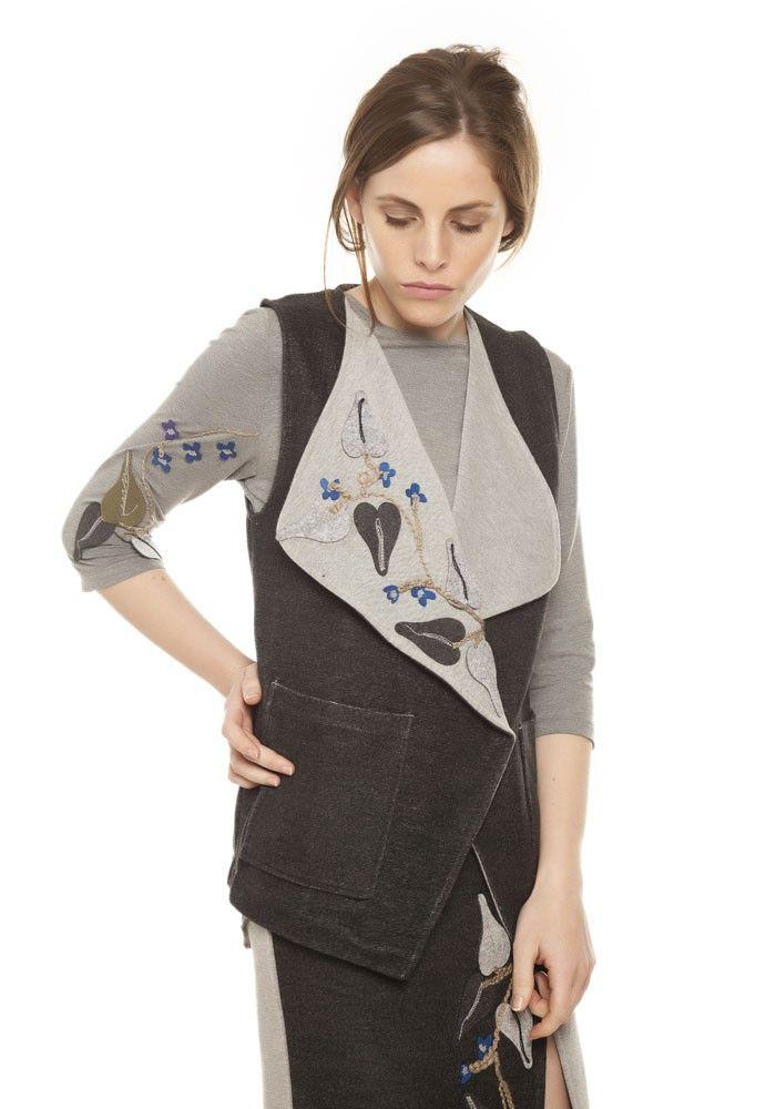 Gilet en tricot interlock de double face anthracite/ gris vigoré avec le revers large et applications de plantes grimpantes en broderie, feutrine et cordon. Poches et fermeture par boutons.