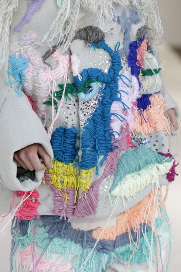 Evelien van Pruissen, 2010: The image is from the collection by Pruissen. The garment is a abstract representation of a face and uses large woollen threads, pastel colours and sequins to further reinforce its abstract nature. There is roughness to the work and this can be seen in variation of stitch length and unfinished quality of the work.