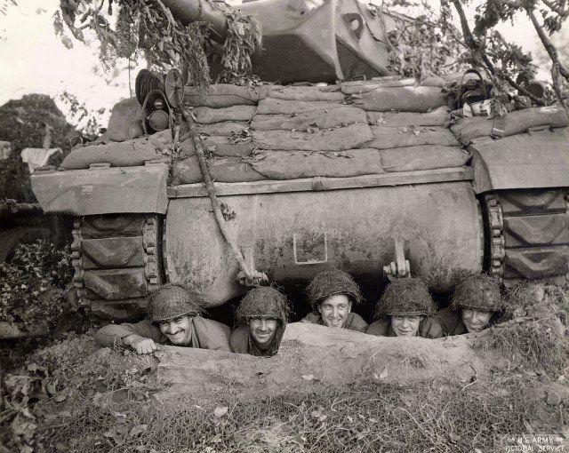 Tank crew takes cover below a M10 Tank Destroyer