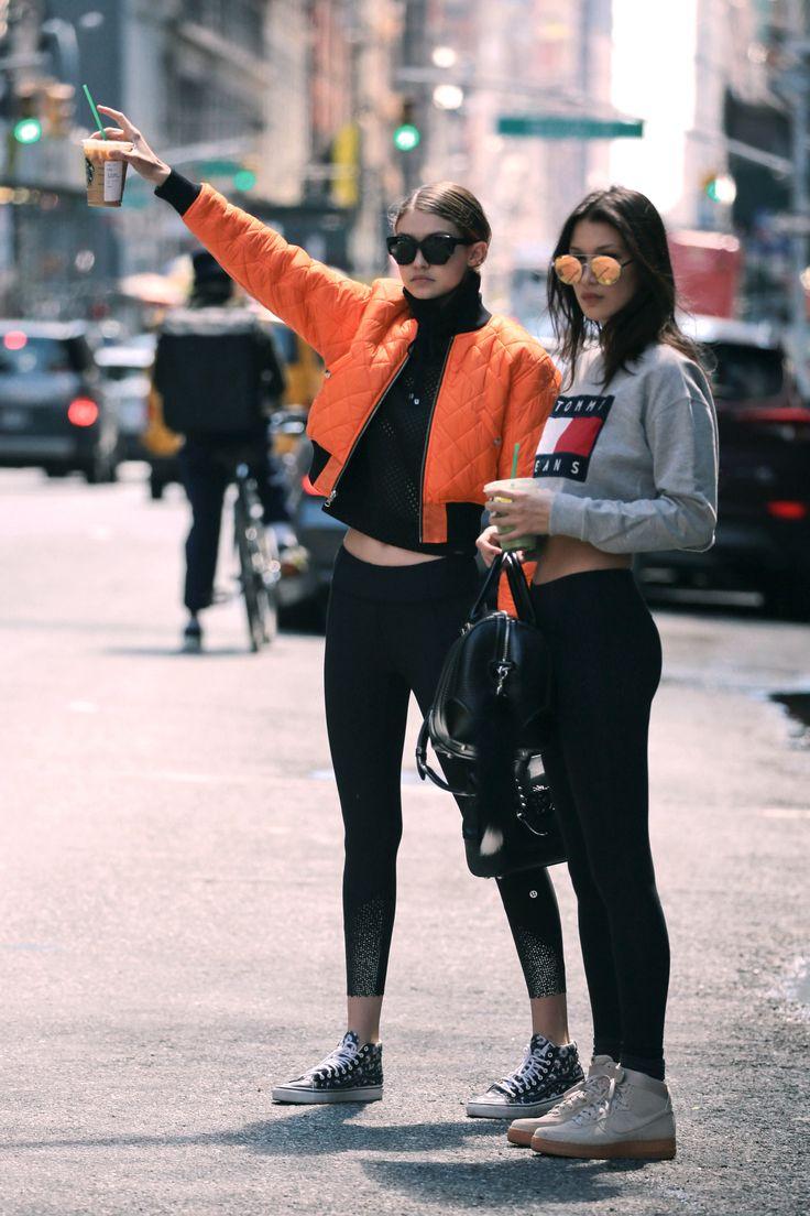Gigi Hadid in leggings, sneakers, a black tank and orange bomber jacket. Bella Hadid in leggings, sneakers, and a cropped Tommy Hilfiger sweatshirt.