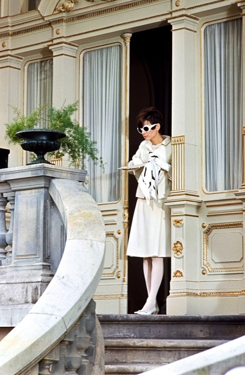 "Audrey Hepburn photographed by Terry O'Neill, in front of the Givenchy's family house, during the filming of ""How to Steal a Million"". Paris (France), 1965.        -Audrey was wearing creations of Givenchy (jacket and skirt of white wool, crepê blouse, stockings, leather handbag and silk scarf), sunglasses of Oliver Goldsmith and Charles Jourdan shoes."