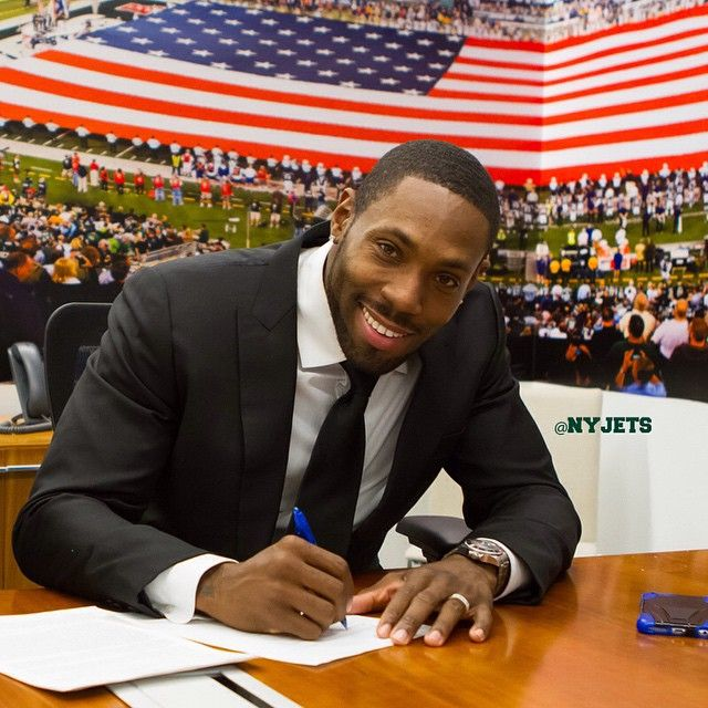 Antonio Cromartie dresses in a classic black-and-white suit and shirt combination while he signs his contract with the New York Jets.