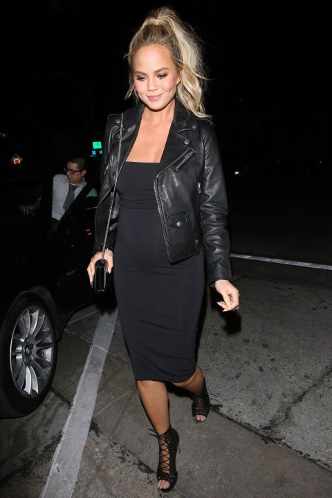 Chrissy Teigen steps out in a black midi dress and leather jacket. See all the model's best maternity style outfits here: