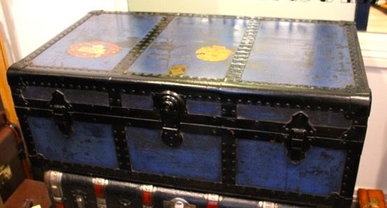 A low 1920's steamer trunk in blue with black trims, locks and hasps