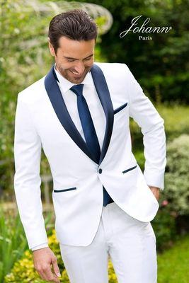 Smoking de mariage blanc véritable, revers en soie marine, gilet creusé à 3 boutons. Chemise à plastron et boutons bleu marine coordonnés. Nœud pap marine.