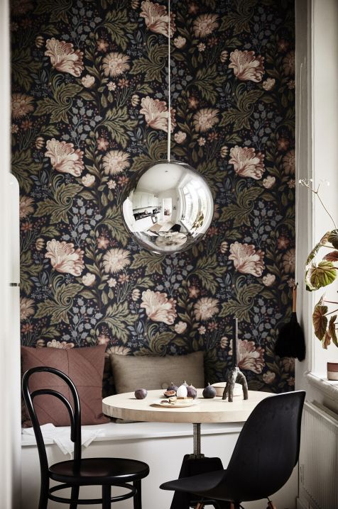 So much to love about this quirky dining nook... the dark floral wallpaper, the smooth reflecting orb chandelier, the two mismatched but surprisingly compatible chairs. Understated Sophistication.