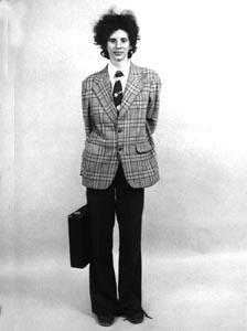 Mariangela Bean   Camicia bianca   con cravatta regimental.   Giacca classica scozzese   con ampie tasche laterali.  Pantaloni neri scampanati.  Scarpe anti-infortunio.  Valigetta diplomatica.
