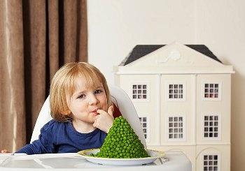 Girl (3-4) eating green peas