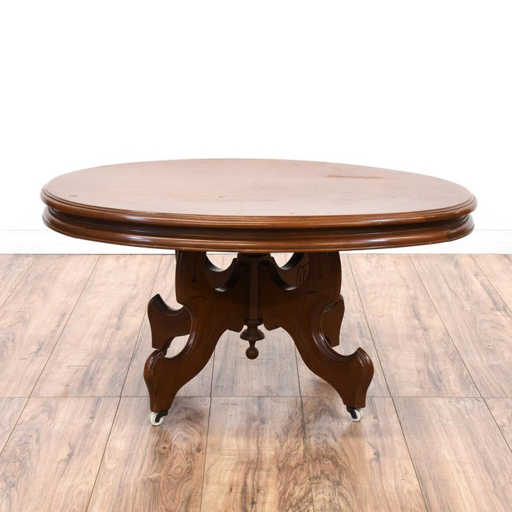 This victorian coffee table is featured in a solid wood with a glossy cherry finish. This coffee table has a round table top, intricate carved base and rolling caster wheels. Perfect for a small living room! #european #tables #coffeetable #sandiegovintage #vintagefurniture