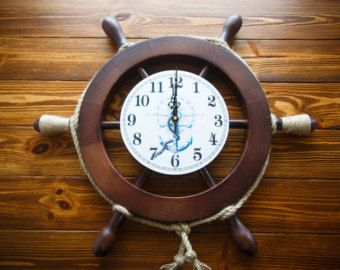 Clock made of natural wood with a pendulum. Watch made in the form of nautical helm and with the pendulum in the shape of an anchor. The product is dyed and dissected several layers of lacquer. The clock mechanism is powered by a single battery, soft, does not knock. The image ship floating in the sea. The size of the wheel with handles 45 cm It will be a good decoration of the room in a nautical theme, a good gift to you or your friends.