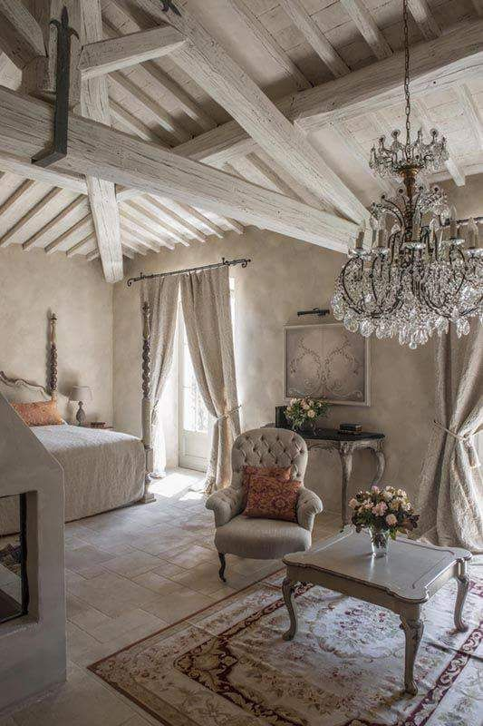 Gorgeous neutral bedroom with rustic exposed beams and glamorous accents, like a crystal chandelier and Persian rug.