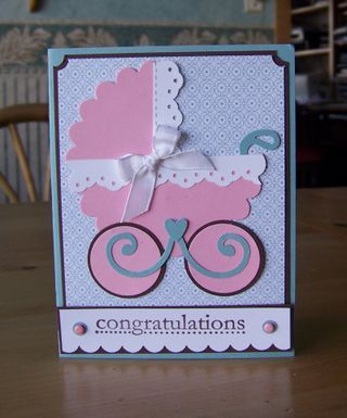 """Punch art baby carriage card; using an eyelet border punch (for carriage trim), 1 1/4 & 1 3/8"""" circle punch (wheels), scalloped punch or die (for the frame), and decorative swirls die (for handle)."""