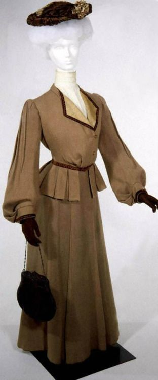 1903 Light brown wool 2-piece walking suit, F.F. Svoboda, St. Louis, MO. Tan wool twill. Jacket with pouched front and box pleated peplum; button and loop closure. Collarless, turned back reverse faced with gold and ivory damask. Very full bishop sleeves. Band cuff with ornamental buttons and brown velvet. Three-gore bias-cut skirt with center front pleated panel.