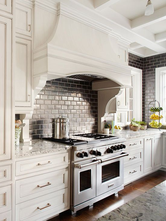 The range area is this room's focal point. With two large decorative brackets, the range hood echoes the furniture-style details featured throughout the room on the cabinetry and the island.