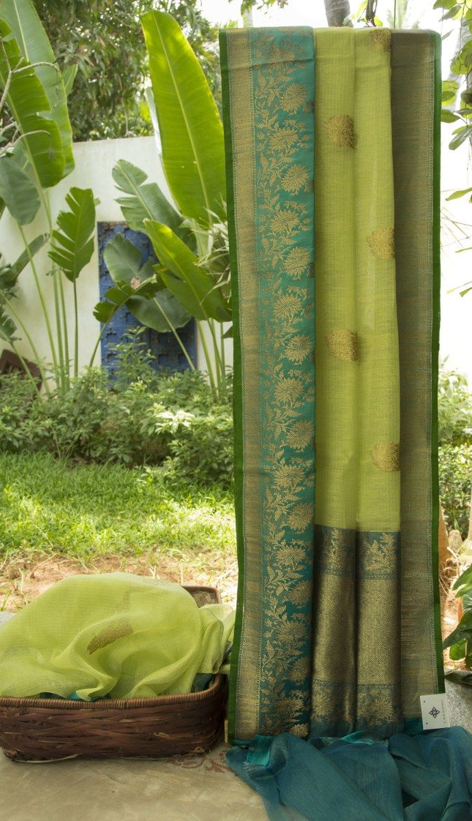 This pear green Benares linen has gold zari bhuttas all over the sari. The selvedge is in emerald green while the border and pallu are in steel blue with an intricate design made with gold zari mak…