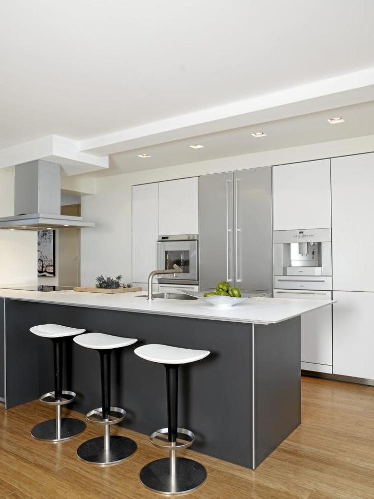 Kjøkkenet ligger midt i leiligheten, med stuen på den ene siden og soverom på den andre. Innredningen er fra Bulthaup, hvitevarene fra Gaggenau. I åpningen mot stuen blir lyset fra takvinduene kastet helt inn til arbeidssonen på kjøkkenet.
