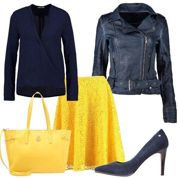 Gonna a campana in giallo con lunghezza fino al ginocchio da abbinare ad una camicetta blu con scollo incrociato. Giacca in finta pelle blu, décolleté a punta sempre in blu. Completa l'outfit borsa a mano in finta pelle gialla che riprende il colore della gonna.