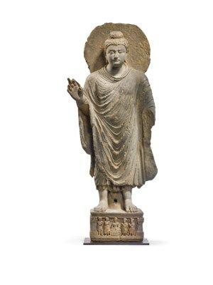 RARE STATUE DE BOUDDHA SHAKYAMUNI EN SCHISTE GRIS ANCIENNE REGION DU GANDHARA, IIEME-IIIEME SIECLE Il est représenté debout en samabhanga sur un piédestal orné d'un bodhisattva assis flanqué d'adorants. Il est vêtu d'une robe monastique. Sa main droite est en abhayamudra. Son visage est empreint de sérénité. Un halo est placé derrière sa tête ; accidents et restaurations. Hauteur : 125 cm. (49 ¼ in.), socle