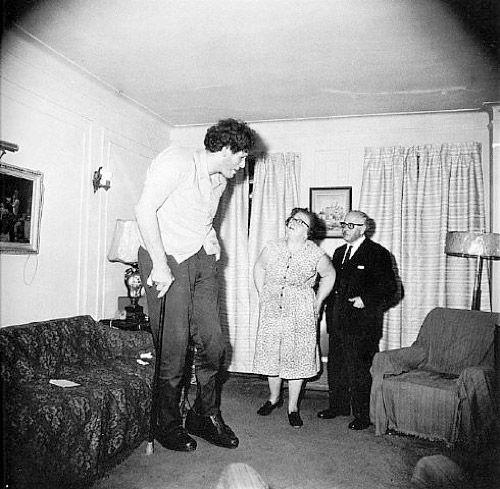 Диана Арбус. Это Эдди Кармел, еврей-гигант с родителями в гостиной их дома в Бронксе. США, 1970