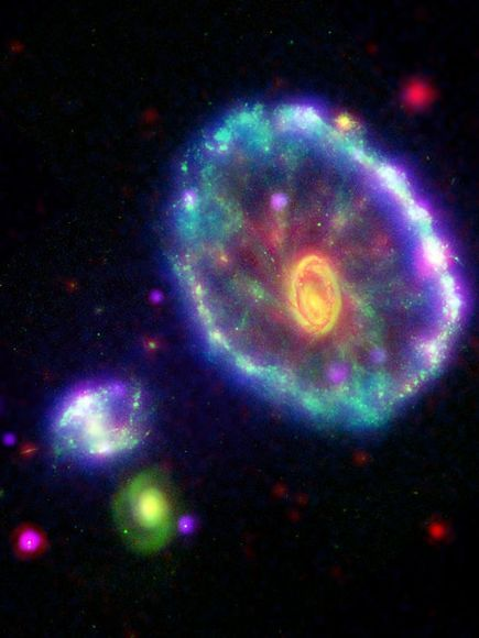 """""""This false-color view of the Cartwheel galaxy was created by combining images captured by four space telescopes: Galaxy Evolution Explorer, Hubble Space Telescope, Spitzer Space Telescope, and Chandra X-ray Observatory. Astronomers think a smaller galaxy, possibly one of two galaxies seen here (bottom left), passed through the center of the Cartwheel galaxy about 100 million years ago."""" via National Geographic"""