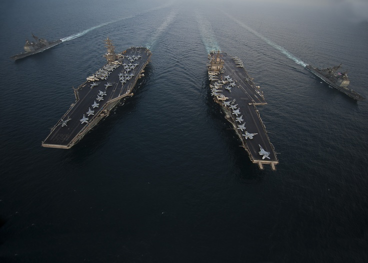U.S. FIFTH FLEET AREA OF RESPONSIBILITY (Sept. 27, 2012) The Aircraft carrier USS Enterprise (CVN 65), center right, the Nimitz-class aircraft carrier USS Dwight D. Eisenhower (CVN 69), and the Ticonderoga-class guided-missile cruisers USS Vicksburg (CG 69), far right, and USS Hue City (CG 66) are underway in formation during a passing exercise. (U.S. Navy photo by Mass Communication Specialist 3rd Class Scott Pittman/Released)