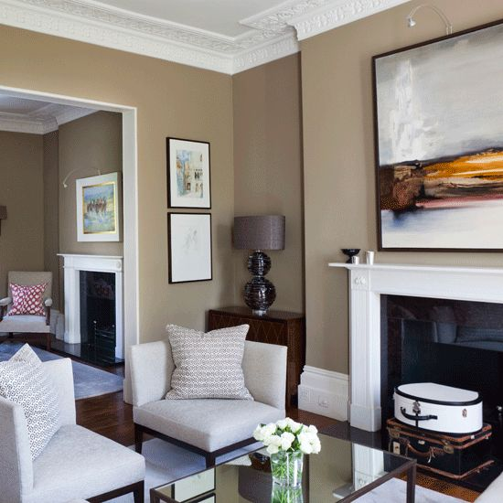 Living room - corner chair away from wall; paint color; white fireplace w/black surround; artwork; symmetry with neighbor room