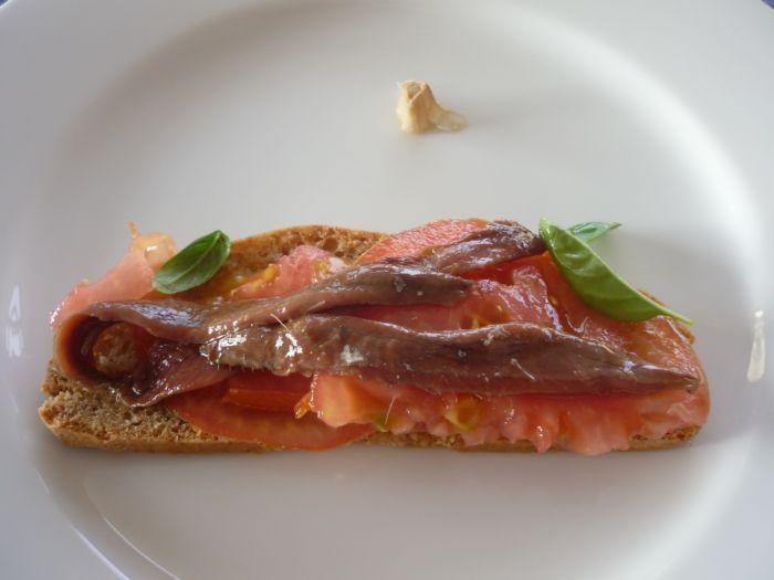 Bread, garlic, tomato, basilicum, Olive Oil and Olasagasti Anchovies.  Clásica tosta frotada con ajo, con tomate, anchoas del Cantábrico y basílico.