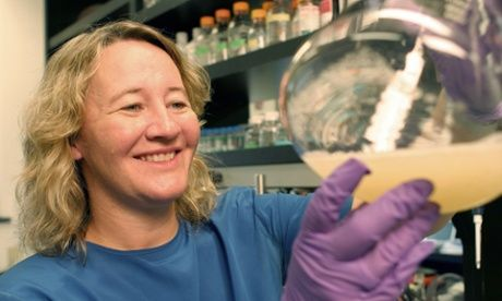 Carol Greider holding a flask of bacteria