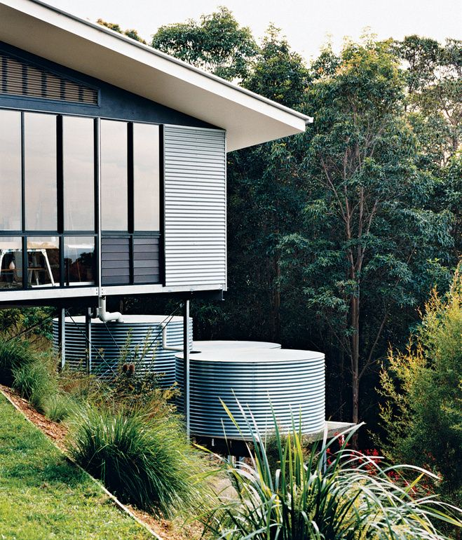 Adrienne Webb and Stefan Dunlop's home in northeastern Australia—a steel-framed glass box clad in strips of spotted gum timber and sheets of fiber cement—Corrugated tin covers their studio and echoes the adjacent corrugated-iron water-storage tanks, which collect and filter rainwater off the roof.
