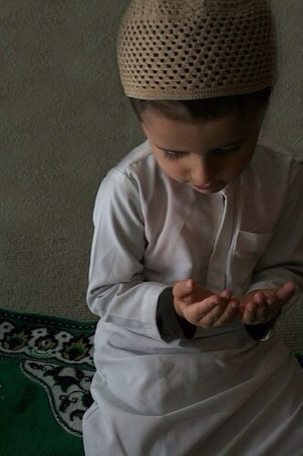 A young boy making dua.
