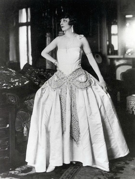 Jane Renouardt in Jeanne Lanvin, 1925. The robe de style, which is often associated with Lanvin, is characterized by its dropped waist and wide skirts designed to resemble court dresses of the 18th century. The style safely hid the figure, which made it comfortable for clients of any age and shape.