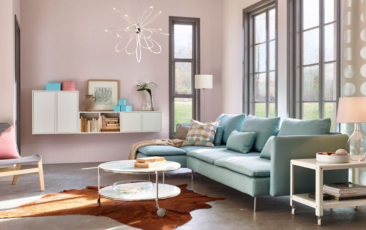 A sunlit living room with a light turquoise three-seat sofa with chaise longue. Combined with a white round coffee table and a trolley, both on castors.