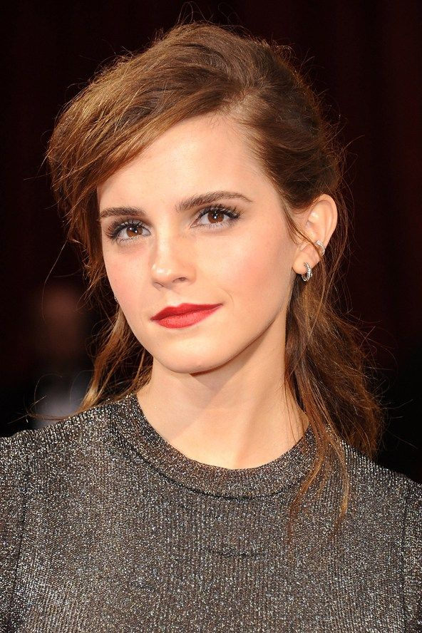 Emma Watson contrasted her polished make-up look by wearing her hair in an artfully messy ponytail.